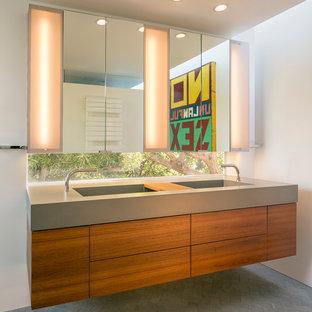 Idee per una stanza da bagno padronale moderna di medie dimensioni con lavabo integrato, ante lisce, ante in legno scuro, top in cemento, WC sospeso, piastrelle grigie, piastrelle in gres porcellanato, pareti bianche e pavimento in gres porcellanato