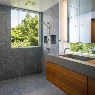 Ispirazione per una stanza da bagno padronale minimalista di medie dimensioni con lavabo integrato, ante lisce, ante in legno scuro, top in cemento, doccia a filo pavimento, WC sospeso, piastrelle grigie, piastrelle in gres porcellanato, pareti bianche e pavimento in gres porcellanato