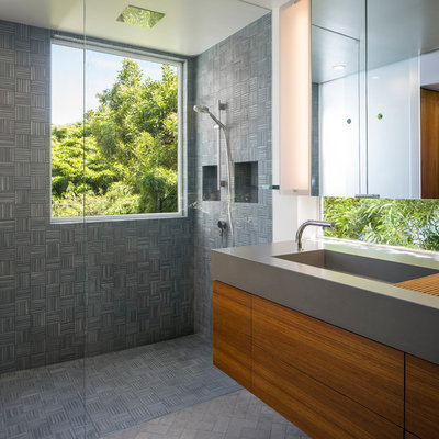 Mid-sized minimalist master gray tile and porcelain tile porcelain tile walk-in shower photo in San Francisco with an integrated sink, flat-panel cabinets, medium tone wood cabinets, concrete countertops, a wall-mount toilet and white walls