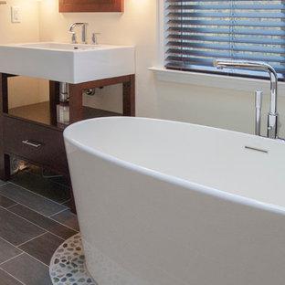Idee per una stanza da bagno padronale etnica di medie dimensioni con lavabo a bacinella, nessun'anta, ante in legno bruno, vasca freestanding, piastrelle grigie, piastrelle di ciottoli e pavimento in gres porcellanato