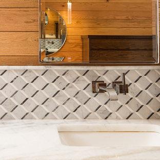 アトランタの中サイズのモダンスタイルのおしゃれなマスターバスルーム (フラットパネル扉のキャビネット、濃色木目調キャビネット、アルコーブ型シャワー、一体型トイレ、白いタイル、大理石タイル、白い壁、大理石の床、オーバーカウンターシンク、大理石の洗面台、白い床、開き戸のシャワー、白い洗面カウンター) の写真