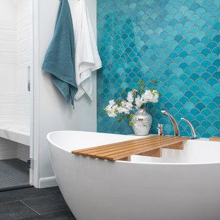 ボストンの大きいエクレクティックスタイルのおしゃれなマスターバスルーム (フラットパネル扉のキャビネット、淡色木目調キャビネット、置き型浴槽、段差なし、一体型トイレ、白いタイル、磁器タイル、白い壁、磁器タイルの床、アンダーカウンター洗面器、人工大理石カウンター、グレーの床、開き戸のシャワー) の写真