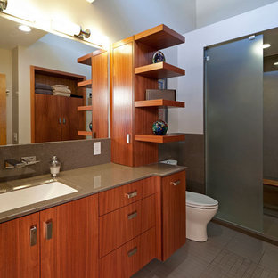 Example of a mid-sized minimalist master ceramic tile and gray tile porcelain tile bathroom design in St Louis with flat-panel cabinets, medium tone wood cabinets, a one-piece toilet, white walls, onyx countertops and an undermount sink