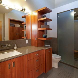 Bild på ett mellanstort funkis en-suite badrum, med keramikplattor, en öppen dusch, släta luckor, skåp i mellenmörkt trä, en toalettstol med hel cisternkåpa, grå kakel, vita väggar, klinkergolv i porslin, bänkskiva i onyx, ett undermonterad handfat och med dusch som är öppen