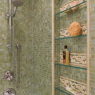 Ejemplo de cuarto de baño principal, mediterráneo, grande, con lavabo bajoencimera, armarios con paneles empotrados, puertas de armario con efecto envejecido, encimera de acrílico, bañera esquinera, combinación de ducha y bañera, sanitario de una pieza, baldosas y/o azulejos verdes, baldosas y/o azulejos de vidrio, paredes beige y suelo de baldosas de porcelana