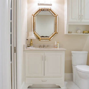 Mid-sized tuscan 3/4 beige tile and ceramic tile ceramic floor and beige floor bathroom photo in Austin with raised-panel cabinets, white cabinets, a two-piece toilet, beige walls, an undermount sink and limestone countertops