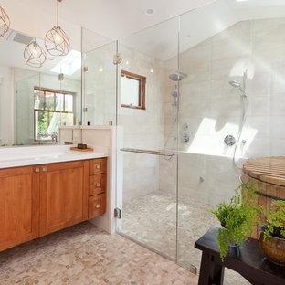На фото: главная ванная комната в средиземноморском стиле с фасадами в стиле шейкер, фасадами цвета дерева среднего тона, душем без бортиков, белыми стенами, полом из галечной плитки, раковиной с несколькими смесителями, серой плиткой, японской ванной, керамической плиткой, столешницей из кварцита, разноцветным полом, белой столешницей и душем с распашными дверями с