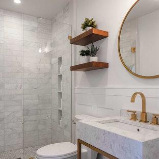 Inspiration för små moderna vitt badrum med dusch, med en dusch i en alkov, en toalettstol med hel cisternkåpa, vit kakel, marmorkakel, vita väggar, marmorbänkskiva, dusch med gångjärnsdörr, öppna hyllor, vita skåp, klinkergolv i porslin, ett konsol handfat och brunt golv