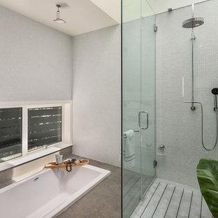 Diseño de cuarto de baño principal, marinero, extra grande, con armarios tipo mueble, puertas de armario naranjas, bañera encastrada, ducha a ras de suelo, paredes blancas, lavabo sobreencimera, suelo gris y ducha con puerta con bisagras