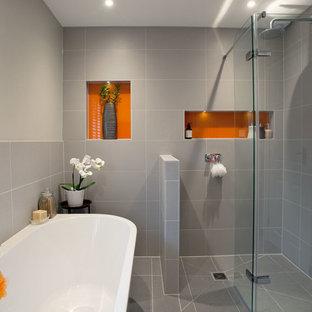 Idee per una stanza da bagno con doccia design di medie dimensioni con zona vasca/doccia separata, piastrelle in ceramica, pareti grigie, pavimento con piastrelle in ceramica, pavimento grigio, porta doccia a battente, vasca freestanding e piastrelle grigie