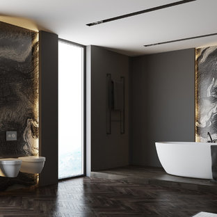 Example of a mid-sized minimalist master gray tile and marble tile dark wood floor and multicolored floor freestanding bathtub design in Los Angeles with a wall-mount toilet and gray walls