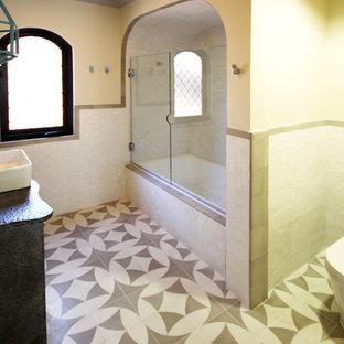 ロサンゼルスの小さい地中海スタイルのおしゃれなバスルーム (浴槽なし) (ベッセル式洗面器、家具調キャビネット、グレーのキャビネット、亜鉛の洗面台、ドロップイン型浴槽、アルコーブ型シャワー、一体型トイレ、白いタイル、白い壁、セラミックタイルの床) の写真