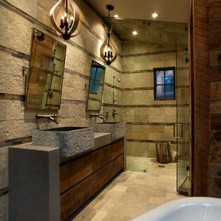 Example of a large mountain style master stone tile, beige tile and brown tile limestone floor and beige floor wet room design in Sacramento with flat-panel cabinets, dark wood cabinets, brown walls, a vessel sink, concrete countertops and a hinged shower door
