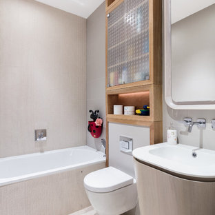 Medium sized contemporary ensuite bathroom in London with a built-in bath, a shower/bath combination, a wall mounted toilet, beige tiles, ceramic tiles, beige walls, ceramic flooring and a console sink.