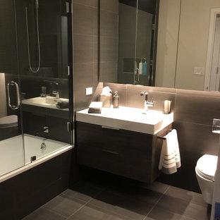 Kleines Modernes Badezimmer En Suite mit flächenbündigen Schrankfronten, braunen Schränken, Badewanne in Nische, Duschnische, Wandtoilette, grauen Fliesen, Keramikfliesen, grauer Wandfarbe, Keramikboden, integriertem Waschbecken, Quarzwerkstein-Waschtisch, grauem Boden, Falttür-Duschabtrennung, weißer Waschtischplatte, Nische, Einzelwaschbecken und schwebendem Waschtisch in New York