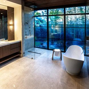Exempel på ett mycket stort modernt vit vitt en-suite badrum, med släta luckor, skåp i ljust trä, ett fristående badkar, en kantlös dusch, en vägghängd toalettstol, grå kakel, stenhäll, grå väggar, klinkergolv i porslin, ett avlångt handfat, marmorbänkskiva, beiget golv och med dusch som är öppen