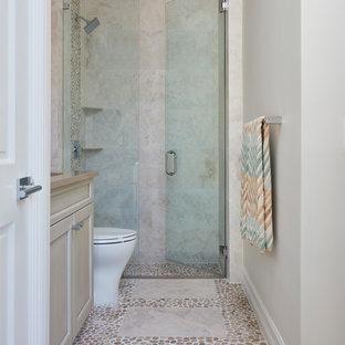 Kleines Modernes Duschbad mit Kassettenfronten, beigen Schränken, bodengleicher Dusche, Toilette mit Aufsatzspülkasten, beigefarbenen Fliesen, Porzellanfliesen, beiger Wandfarbe, Unterbauwaschbecken, Quarzwerkstein-Waschtisch, Falttür-Duschabtrennung, Kiesel-Bodenfliesen und beigem Boden in Miami