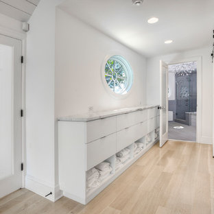 Mid-sized coastal master light wood floor and beige floor bathroom photo in New York with flat-panel cabinets, white cabinets, a one-piece toilet, white walls, a wall-mount sink, marble countertops, a hinged shower door and white countertops