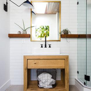 Стильный дизайн: маленькая ванная комната в современном стиле с открытыми фасадами, фасадами цвета дерева среднего тона, угловым душем, белой плиткой, белыми стенами, душевой кабиной, настольной раковиной, душем с распашными дверями, белой столешницей, бетонным полом и серым полом - последний тренд
