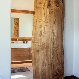 Foto de cuarto de baño principal, minimalista, de tamaño medio, con armarios con paneles lisos, puertas de armario de madera oscura, ducha abierta, sanitario de una pieza, baldosas y/o azulejos de mármol, suelo de cemento, lavabo encastrado, encimera de mármol, suelo gris, ducha abierta y paredes amarillas