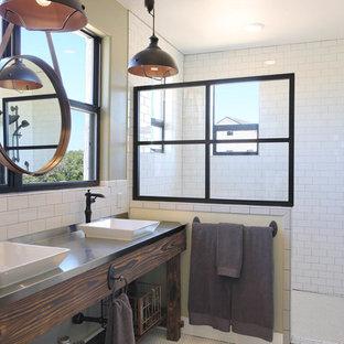 Foto di una stanza da bagno country con piastrelle bianche, pareti bianche, lavabo a bacinella, top in acciaio inossidabile e porta doccia a battente