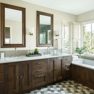 Modelo de cuarto de baño principal, rústico, grande, con armarios estilo shaker, puertas de armario marrones, bañera encastrada, paredes blancas, lavabo bajoencimera, suelo gris y encimeras blancas