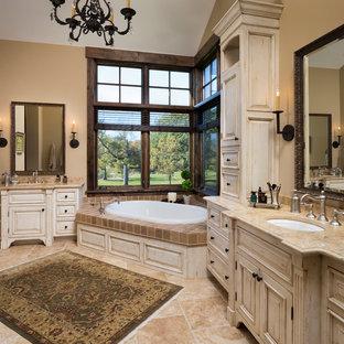 Idéer för att renovera ett stort rustikt en-suite badrum, med ett undermonterad handfat, luckor med upphöjd panel, skåp i slitet trä, marmorbänkskiva, ett platsbyggt badkar, beige kakel, stenkakel, beige väggar, travertin golv och beiget golv