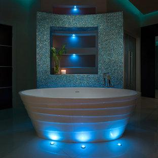 オーランドの巨大なコンテンポラリースタイルのおしゃれなマスターバスルーム (オーバーカウンターシンク、フラットパネル扉のキャビネット、ターコイズのキャビネット、珪岩の洗面台、置き型浴槽、アルコーブ型シャワー、一体型トイレ、白い壁、磁器タイルの床) の写真