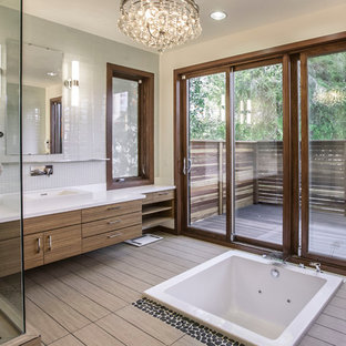 This is an example of a contemporary ensuite bathroom in Los Angeles with flat-panel cabinets, dark wood cabinets, a built-in bath, a corner shower, beige tiles, brown tiles, multi-coloured walls and a built-in sink.