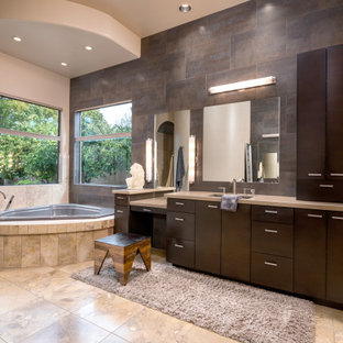 Example of a trendy master multicolored tile multicolored floor and single-sink corner bathtub design in Phoenix with flat-panel cabinets, medium tone wood cabinets, white walls, an undermount sink, beige countertops and a built-in vanity