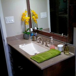 Modelo de cuarto de baño principal, moderno, pequeño, con lavabo integrado, armarios estilo shaker, puertas de armario de madera en tonos medios, encimera de ónix, bañera encastrada, combinación de ducha y bañera, sanitario de una pieza, baldosas y/o azulejos marrones, baldosas y/o azulejos de porcelana, paredes grises y suelo de baldosas de porcelana
