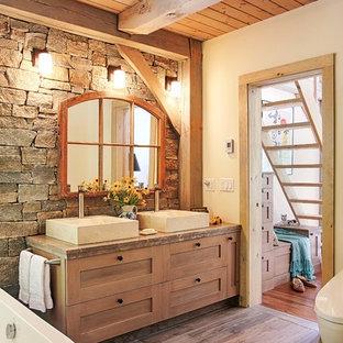 Idéer för stora lantliga beige en-suite badrum, med skåp i mellenmörkt trä, ett fristående badkar, en toalettstol med hel cisternkåpa, beige kakel, vita väggar, klinkergolv i porslin, ett fristående handfat, marmorbänkskiva, skåp i shakerstil, stenkakel och brunt golv