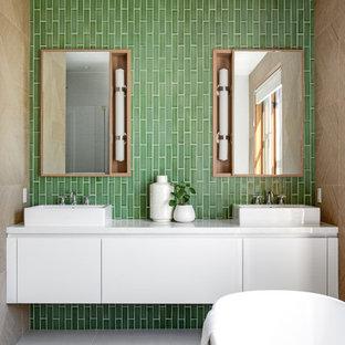 Inredning av ett modernt mellanstort vit vitt en-suite badrum, med släta luckor, vita skåp, ett fristående badkar, grön kakel, keramikplattor, gröna väggar, ett fristående handfat, bänkskiva i kvartsit, cementgolv och grått golv