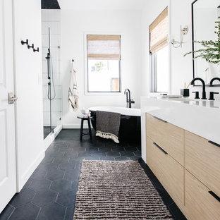 フェニックスの中くらいの北欧スタイルのおしゃれなマスターバスルーム (フラットパネル扉のキャビネット、淡色木目調キャビネット、置き型浴槽、アルコーブ型シャワー、白い壁、セラミックタイルの床、アンダーカウンター洗面器、珪岩の洗面台、黒い床、開き戸のシャワー、白い洗面カウンター) の写真