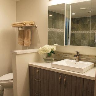 Modelo de cuarto de baño con ducha, actual, pequeño, con armarios con paneles lisos, puertas de armario grises, encimera de vidrio reciclado, ducha empotrada, sanitario de una pieza, baldosas y/o azulejos beige, baldosas y/o azulejos de porcelana, paredes grises, suelo de baldosas de porcelana, lavabo de seno grande y ducha con puerta con bisagras