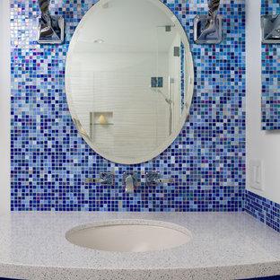 Ejemplo de cuarto de baño infantil, costero, de tamaño medio, con armarios con paneles lisos, puertas de armario azules, bañera empotrada, combinación de ducha y bañera, sanitario de una pieza, baldosas y/o azulejos azules, baldosas y/o azulejos de vidrio, paredes blancas, suelo de baldosas de cerámica, lavabo bajoencimera y encimera de cuarzo compacto