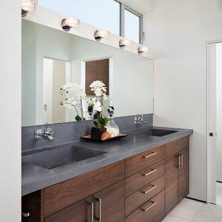 Diseño de cuarto de baño principal, minimalista, extra grande, con lavabo integrado, armarios con paneles lisos, puertas de armario de madera en tonos medios, paredes blancas, ducha empotrada, suelo de baldosas de porcelana, encimera de cemento, suelo beige, ducha con puerta con bisagras y encimeras grises