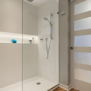 Photo of a small modern shower room in Minneapolis with flat-panel cabinets, brown cabinets, a built-in shower, a one-piece toilet, white tiles, grey walls, vinyl flooring, a wall-mounted sink, brown floors, an open shower and white worktops.
