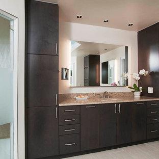 Cette image montre une grand salle de bain principale minimaliste avec une douche d'angle, un lavabo encastré, une cabine de douche à porte battante, un placard à porte plane, des portes de placard en bois sombre, un mur blanc, un sol en carrelage de porcelaine, un plan de toilette en granite et un sol gris.