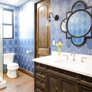Example of a tuscan 3/4 blue tile light wood floor corner shower design in Los Angeles with shaker cabinets, dark wood cabinets, a two-piece toilet, blue walls and an undermount sink