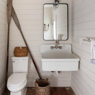 Immagine di una stanza da bagno con doccia country di medie dimensioni con WC monopezzo, piastrelle bianche, pareti bianche e pavimento in mattoni