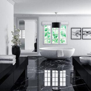 Неиссякаемый источник вдохновения для домашнего уюта: большая главная ванная комната в стиле модернизм с фасадами в стиле шейкер, черными фасадами, отдельно стоящей ванной, душем в нише, унитазом-моноблоком, черно-белой плиткой, белыми стенами, мраморным полом, консольной раковиной, столешницей из кварцита, черным полом, душем с распашными дверями, черной столешницей, нишей, тумбой под одну раковину, встроенной тумбой, сводчатым потолком и панелями на части стены