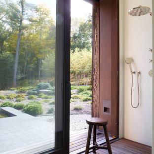 Example of a dark wood floor and brown floor doorless shower design in New York with white walls