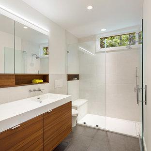 Kleines Modernes Badezimmer En Suite mit flächenbündigen Schrankfronten, braunen Schränken, bodengleicher Dusche, Wandtoilette, gelben Fliesen, Porzellanfliesen, weißer Wandfarbe, Porzellan-Bodenfliesen, integriertem Waschbecken, Mineralwerkstoff-Waschtisch, grauem Boden und Falttür-Duschabtrennung in Baltimore