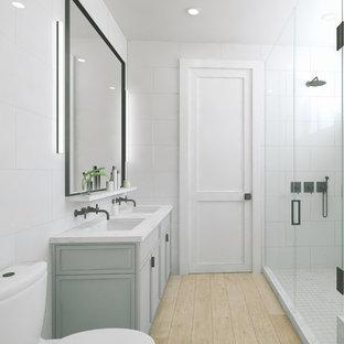 Diseño de cuarto de baño principal, moderno, grande, con armarios con paneles empotrados, encimera de mármol, baldosas y/o azulejos blancos, baldosas y/o azulejos de porcelana, ducha abierta, sanitario de pared, paredes blancas, suelo de madera clara, puertas de armario grises y lavabo bajoencimera