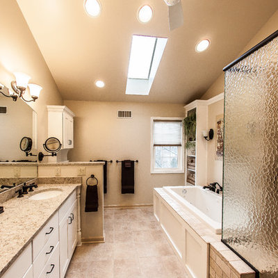 Bathroom - mid-sized traditional master beige tile and porcelain tile porcelain tile and brown floor bathroom idea in Other with an undermount sink, white cabinets, flat-panel cabinets, a one-piece toilet, white walls, quartz countertops and a hinged shower door