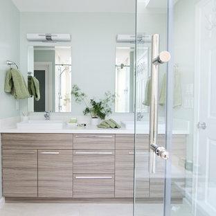 Diseño de cuarto de baño principal, moderno, de tamaño medio, con armarios con paneles lisos, puertas de armario de madera clara, bañera encastrada, ducha doble, sanitario de una pieza, baldosas y/o azulejos beige, baldosas y/o azulejos de porcelana, paredes verdes, suelo de baldosas de porcelana, lavabo sobreencimera y encimera de cuarzo compacto