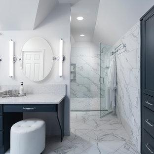 バーミングハムの大きいトランジショナルスタイルのおしゃれなマスターバスルーム (レイズドパネル扉のキャビネット、青いキャビネット、大型浴槽、段差なし、一体型トイレ、白いタイル、セラミックタイル、白い壁、セラミックタイルの床、オーバーカウンターシンク、珪岩の洗面台、白い床、開き戸のシャワー) の写真