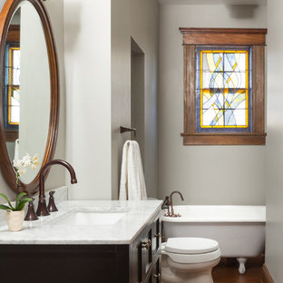 Inspiration for a small transitional master medium tone wood floor claw-foot bathtub remodel in Atlanta with black cabinets, gray walls, an undermount sink, quartzite countertops and furniture-like cabinets
