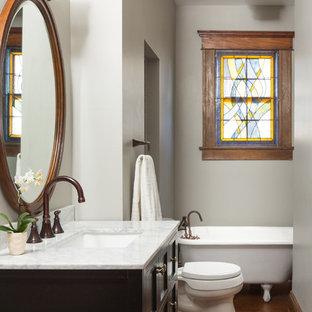 Cette photo montre une petite salle de bain principale chic avec des portes de placard noires, une baignoire sur pieds, un mur gris, un sol en bois brun, un lavabo encastré, un plan de toilette en quartz et un placard en trompe-l'oeil.